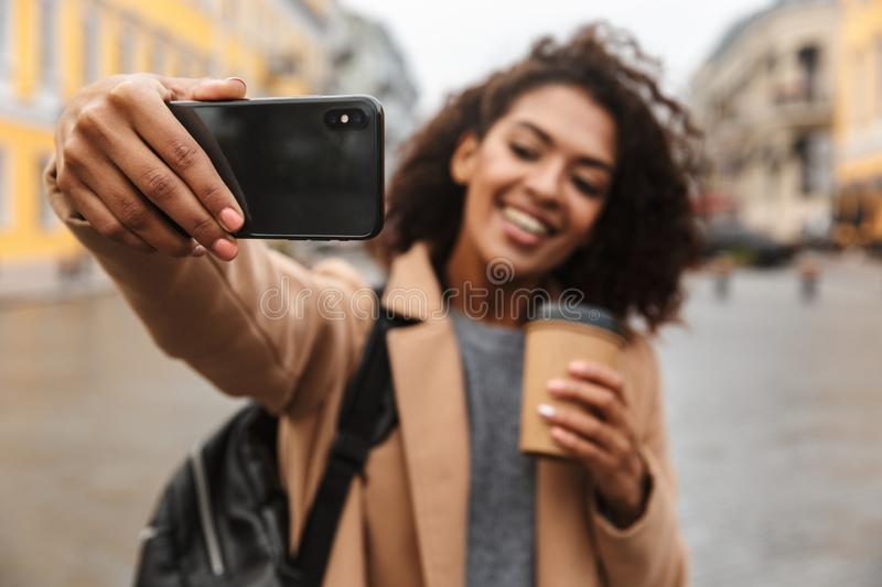 Cheerful young african woman wearing coat walking. Outdoors, holding takeaway coffee cup, taking a selfie stock photo