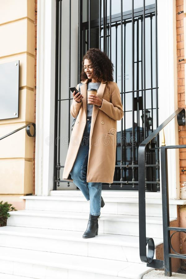 Cheerful young african woman wearing coat walking. Outdoors, holding takeaway coffee cup, using mobile phone stock photos