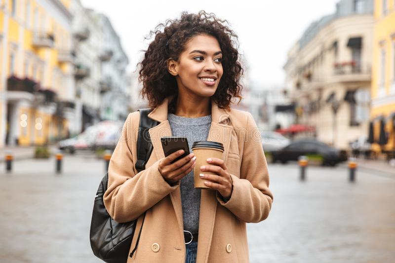 Cheerful young african woman wearing coat walking. Outdoors, holding takeaway coffee cup, using mobile phone royalty free stock photo