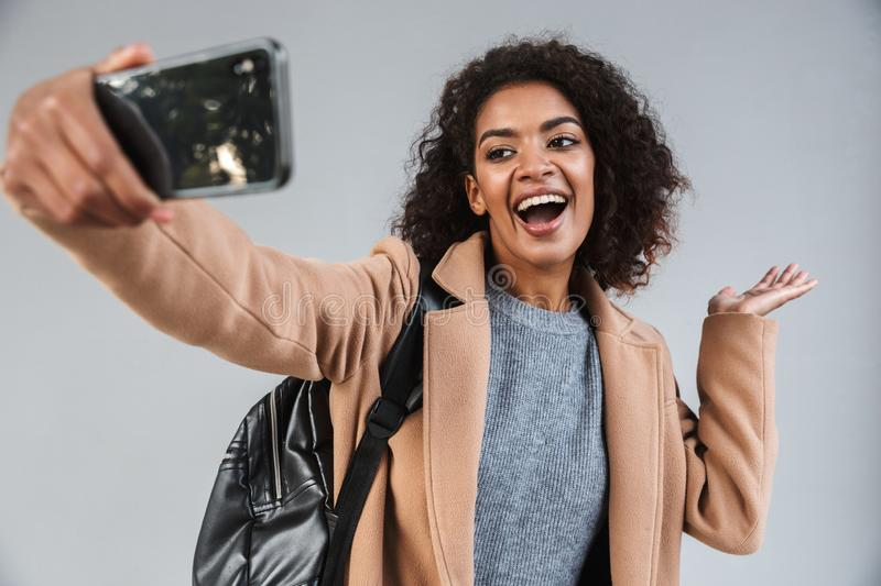 Cheerful young african woman wearing coat walking. Outdoors, taking a selfie stock images