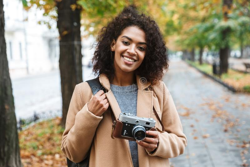 Cheerful young african woman wearing coat walking. Outdoors, holding photo camera royalty free stock photo