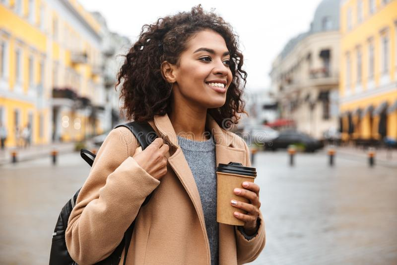 Cheerful young african woman wearing coat walking. Outdoors, holding takeaway coffee cup stock images