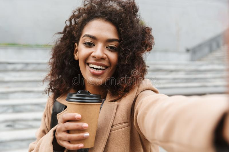Cheerful young african woman wearing coat walking. Outdoors, holding takeaway coffee cup, taking a selfie royalty free stock image