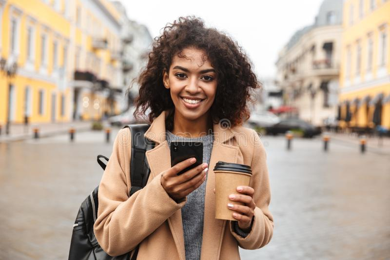 Cheerful young african woman wearing coat walking. Outdoors, holding takeaway coffee cup, using mobile phone stock photo