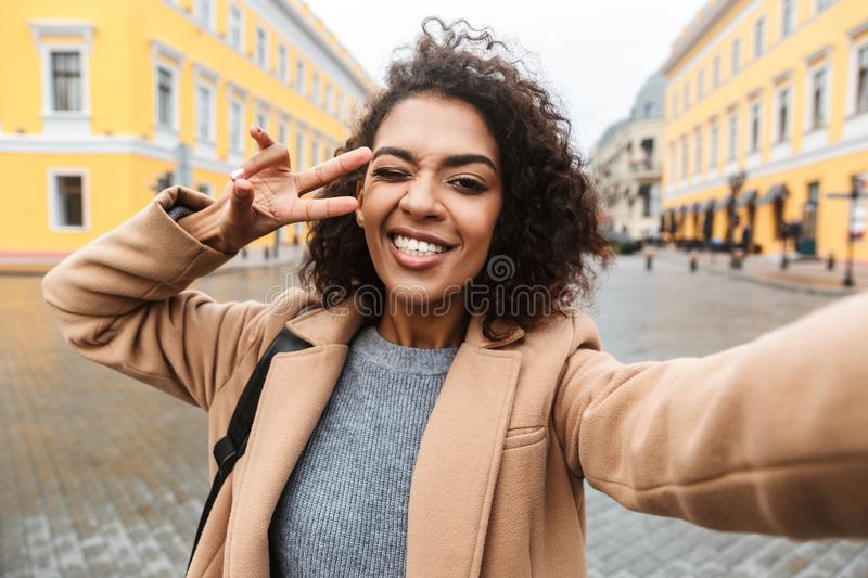 Cheerful young african woman wearing coat walking. Outdoors, taking a selfie stock image