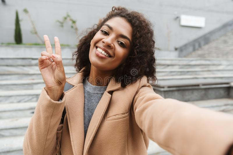 Cheerful young african woman wearing coat walking. Outdoors, taking a selfie royalty free stock photo