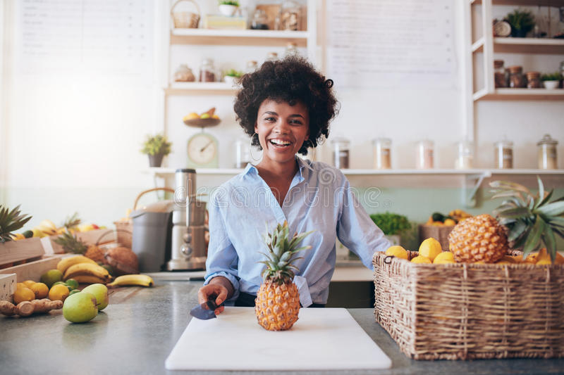 Cheerful young african woman working at juice bar stock photos