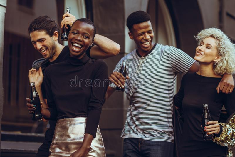 Multi-ethnic group of friends hanging out in the city. Cheerful young african women walking in the city with friends. Multi-ethnic group of friends hanging out stock images