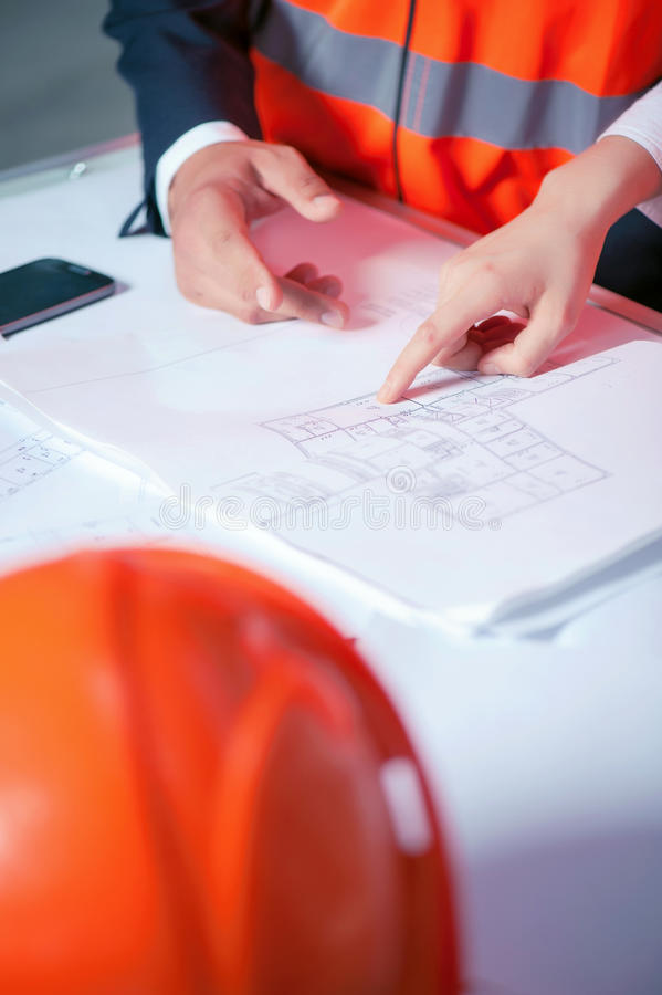 Cheerful young architects are working on a new. Close up of arms of professional engineers. They are discussing a plan of building. The workers are standing near stock photography