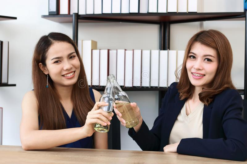 Cheerful young Asian business partners clicking bottle of wine in office. Successful and celebration concept royalty free stock photos