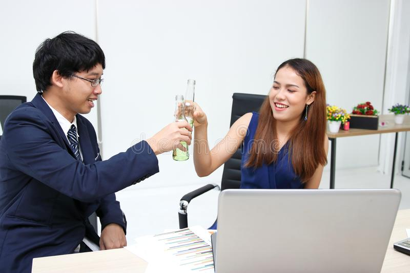 Cheerful young Asian business partners clinking bottle of wine in office. Successful and celebration concept royalty free stock image
