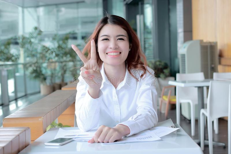 Cheerful young Asian business woman holding two finger as sign as fighting with job at office. Cheerful young Asian business woman holding two finger as sign as royalty free stock photo