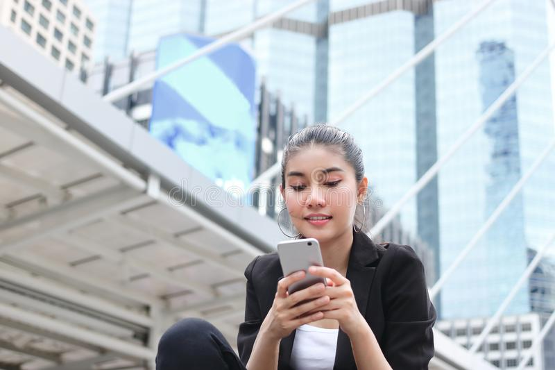 Cheerful young Asian business woman with mobile smart phone in urban background. Internet of things concept royalty free stock image