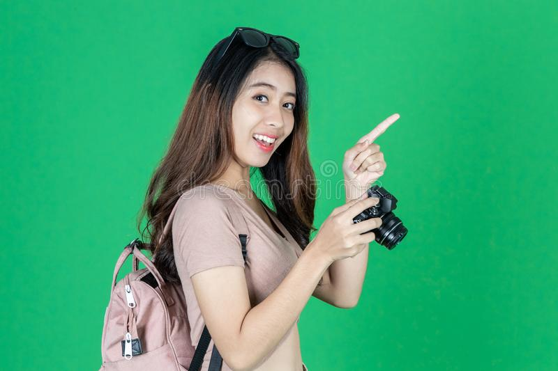 Cheerful young Asian woman with bag and digital camera ready enjoy travel over green isolated background stock photos