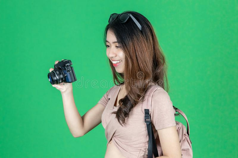Cheerful young Asian woman with bag and digital camera ready enjoy travel over green isolated background stock photo