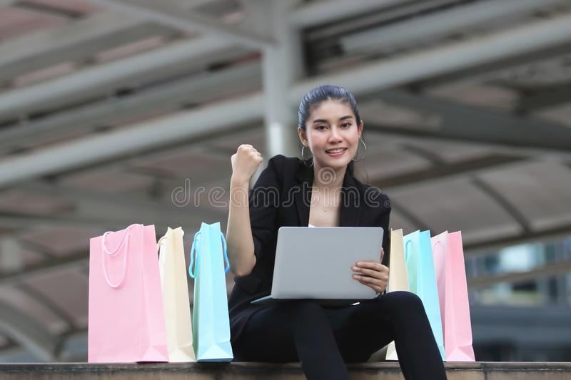 Cheerful young Asian woman with colorful shopping bag and laptop sitting at outdoors. Cheerful young Asian woman with colorful shopping bag and laptop sitting stock image