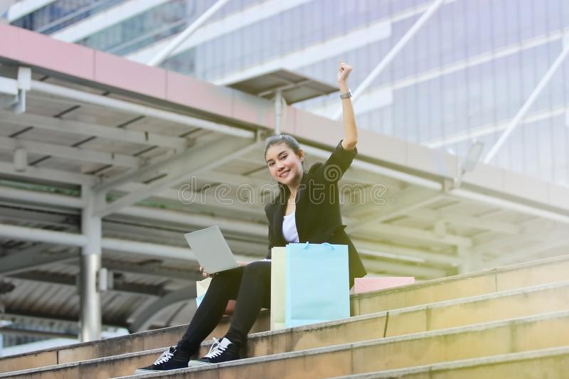 Cheerful young Asian woman with colorful shopping bag and laptop sitting at outdoors. Cheerful young Asian woman with colorful shopping bag and laptop sitting stock photography