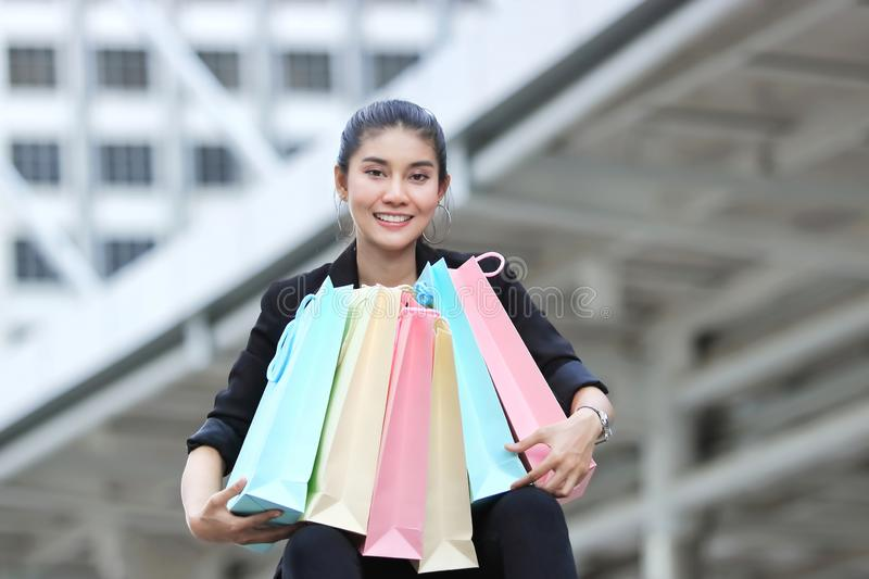 Cheerful young Asian woman with colorful shopping bag in modern city.  stock images