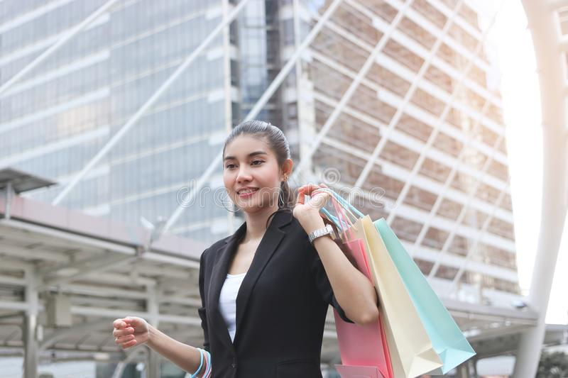 Cheerful young Asian woman with colorful shopping bag in modern city. Cheerful young Asian woman with colorful shopping bag in modern city stock photo
