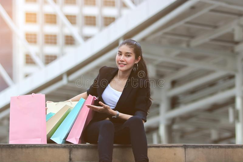 Cheerful young Asian woman with colorful shopping bag in modern city stock images