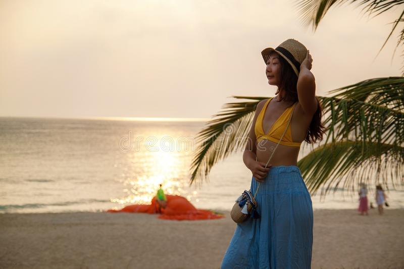 Cheerful young asian woman near palm tree on beach at sunset. Cheerful young asian woman near palm tree on beach at sunset on vacation royalty free stock images