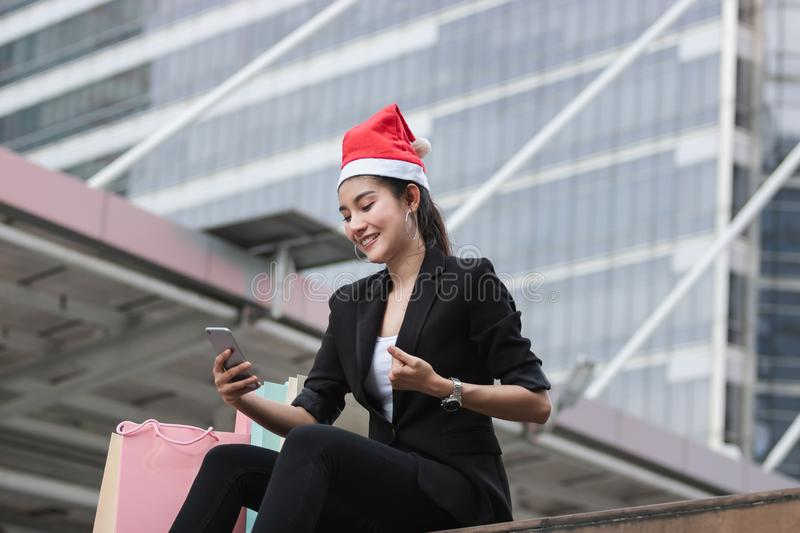 Cheerful young Asian woman with santa hat and colorful shopping bag using mobile smart phone for shopping online for christmas gif. Ts stock photography