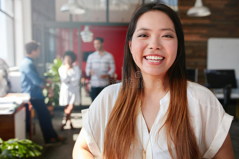 Cheerful young asian woman standing in office royalty free stock photos