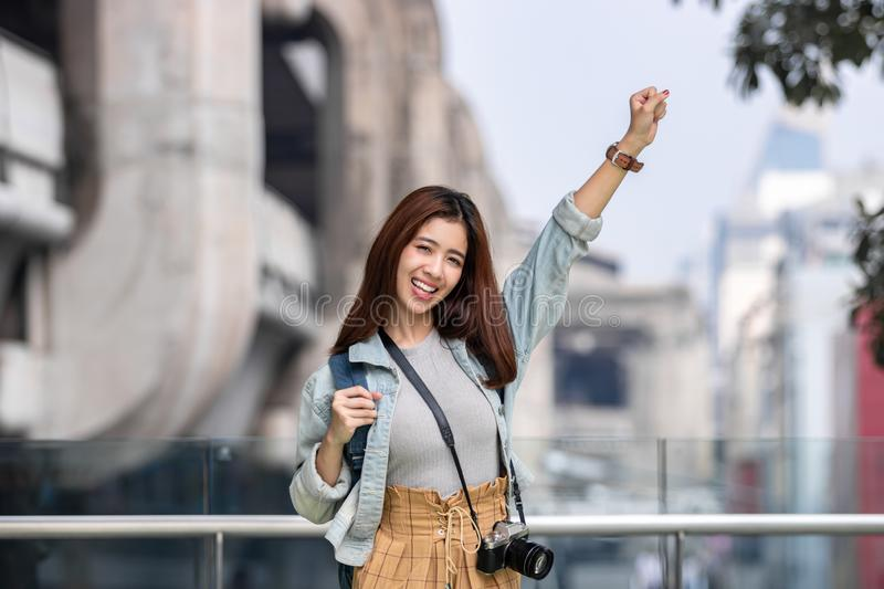 Cheerful young Asian woman tourist raising hands in urban city. Travel and vacation concept royalty free stock photo