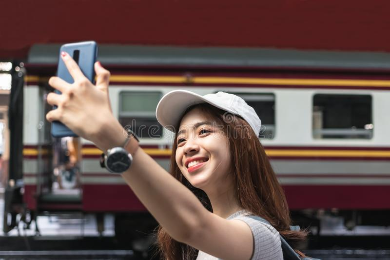 Cheerful young Asian woman traveler with backpack taking a photo or selfie in train station. Travel lifestyle concept stock photography