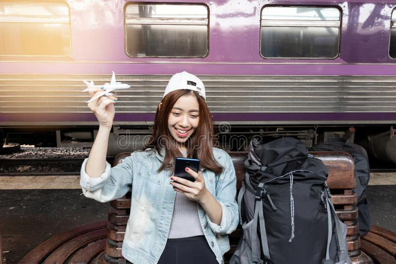 Cheerful young Asian woman traveler with model train sitting on bench waiting for arriving train at station royalty free stock image