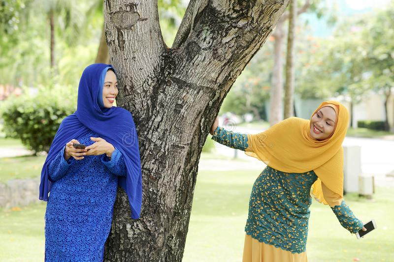 Cheerful islamic women playing in park stock images