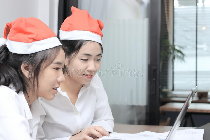 Cheerful young Asian women in Santa hats shopping online with laptop in living room at home. Merry Christmas and happy holidays co. Ncept stock photo