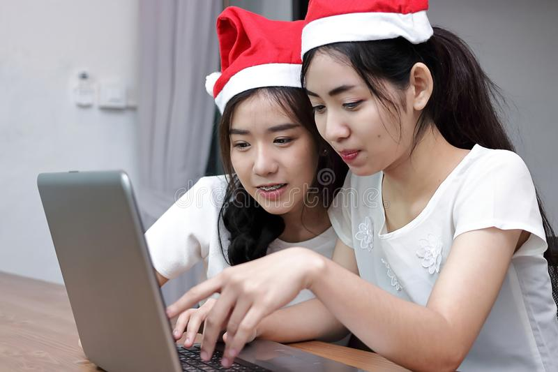 Cheerful young Asian women in Santa hats shopping online with laptop in living room at home. Merry Christmas and happy new year co. Ncept royalty free stock image