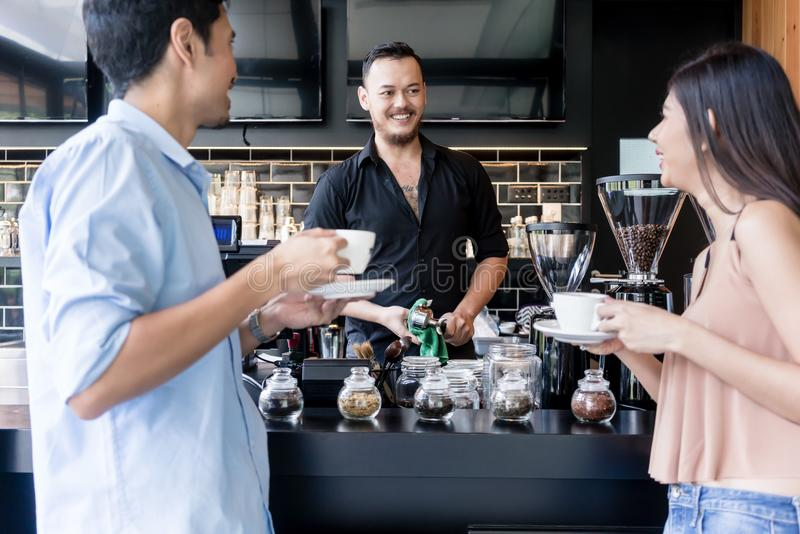 Cheerful young bartender cleaning the coffee maker while talking stock photography