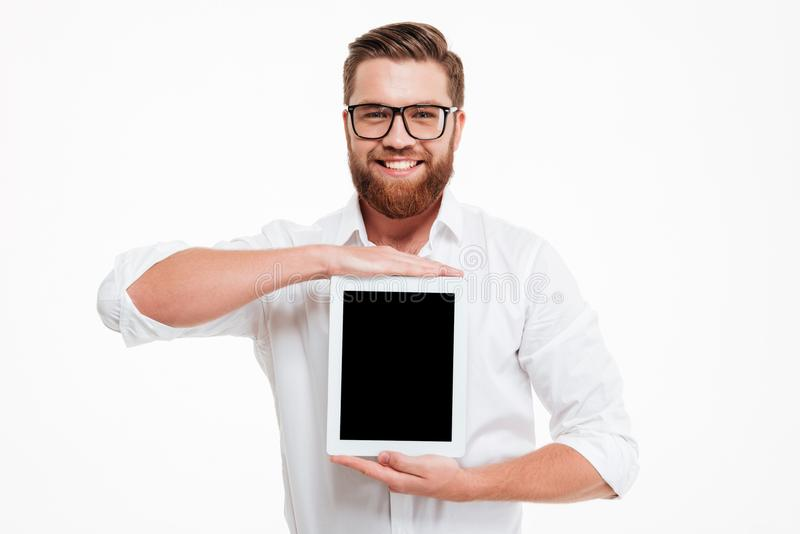 Cheerful young bearded man showing display of tablet computer. stock photo