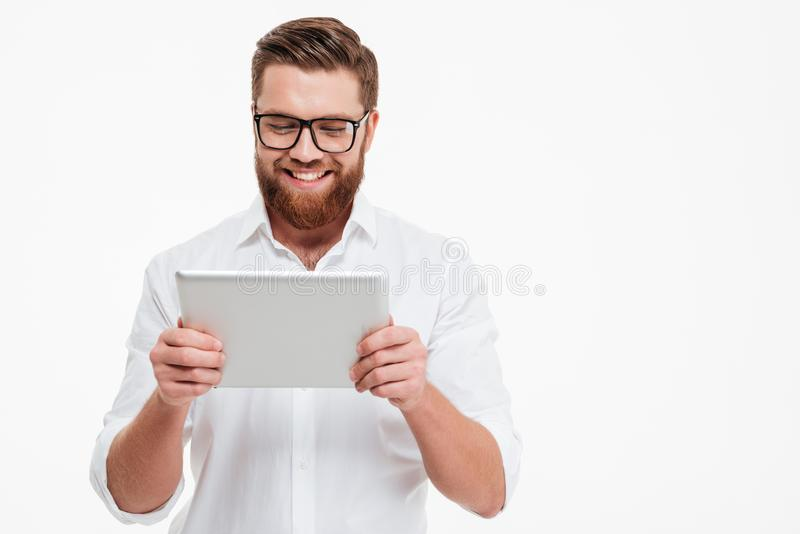 Cheerful young bearded man using tablet computer. Picture of cheerful young bearded man standing near copyspace over white wall background isolated. Looking stock images