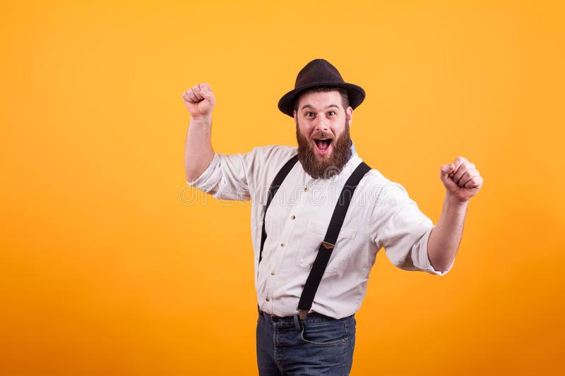 Cheerful young bearded man wearing a hat and smiling looking at the camera over yellow background royalty free stock images