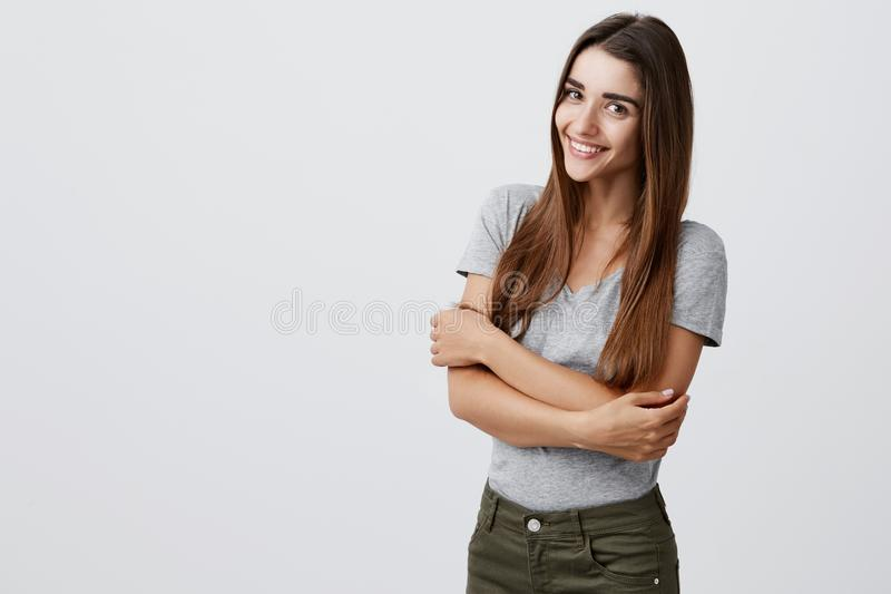 Cheerful young beautiful brunette caucasian student girl with long hair in casual stylish outfit smiling brightly. Holding hands together, posing for stock photography