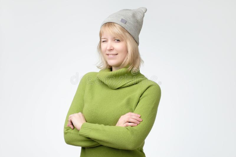 Cheerful young beautiful girl in green sweater and hat smiling winking. Looking at camera over white background royalty free stock photography