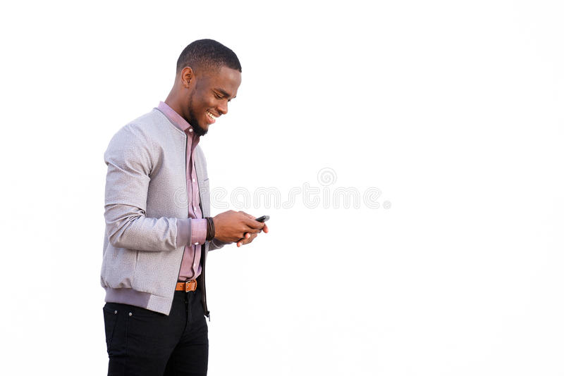 Cheerful young black guy sending text message. Side portrait of a cheerful young black guy sending text message on mobile phone against white background stock image