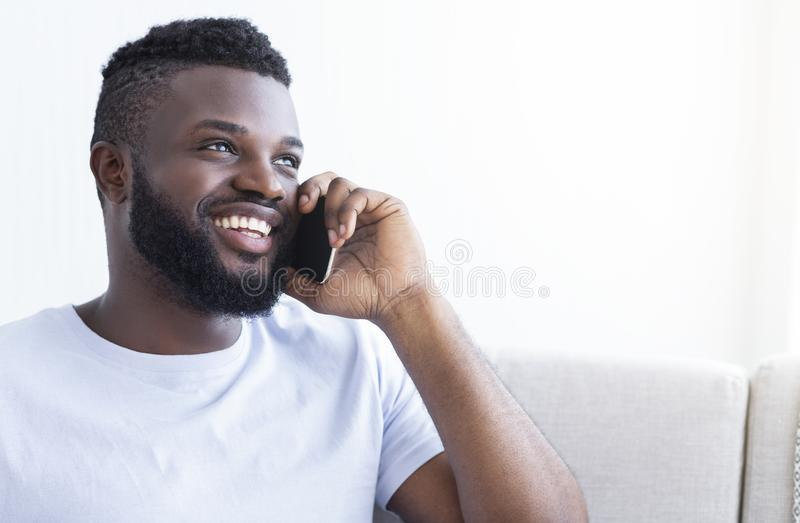 Cheerful young black man talking on smartphone royalty free stock images