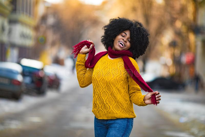 Cheerful young black woman is smiling to the city street stock photo