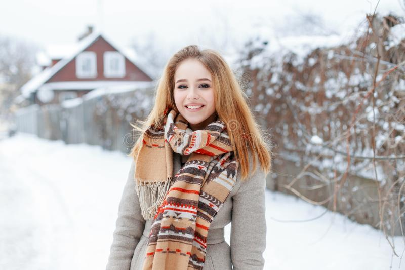 Cheerful young blond woman with a beautiful smile and natural make-up in a gray winter coat with a vintage woolen scarf royalty free stock photos