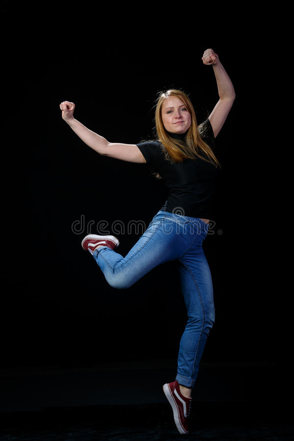 Cheerful young blonde dancing on a black background. Cheerful young blonde, standing on one leg. On a black background stock photography