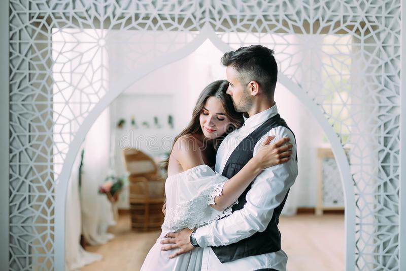 Cheerful young bride smiling and hugging groom while he kisses her in the head and embraces her waist. Beautiful royalty free stock photography