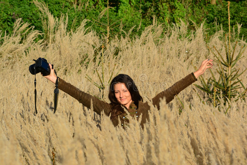 Cheerful, young brunette with DSLR in autumn meadow royalty free stock photo