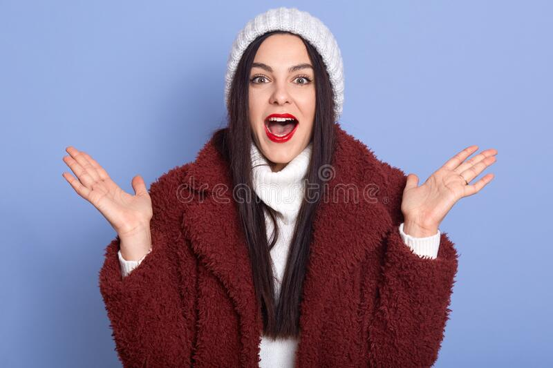 Cheerful young brunette woman girl wearing fur coat posing isolated over blue wall background, lady with red lips and opened mouth stock image