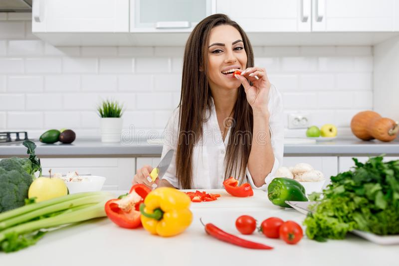 Cheerful Young Brunette Woman Tasting Bell Pepper royalty free stock images