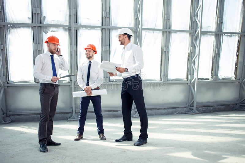 Cheerful young builders are discussing the plan of stock photography