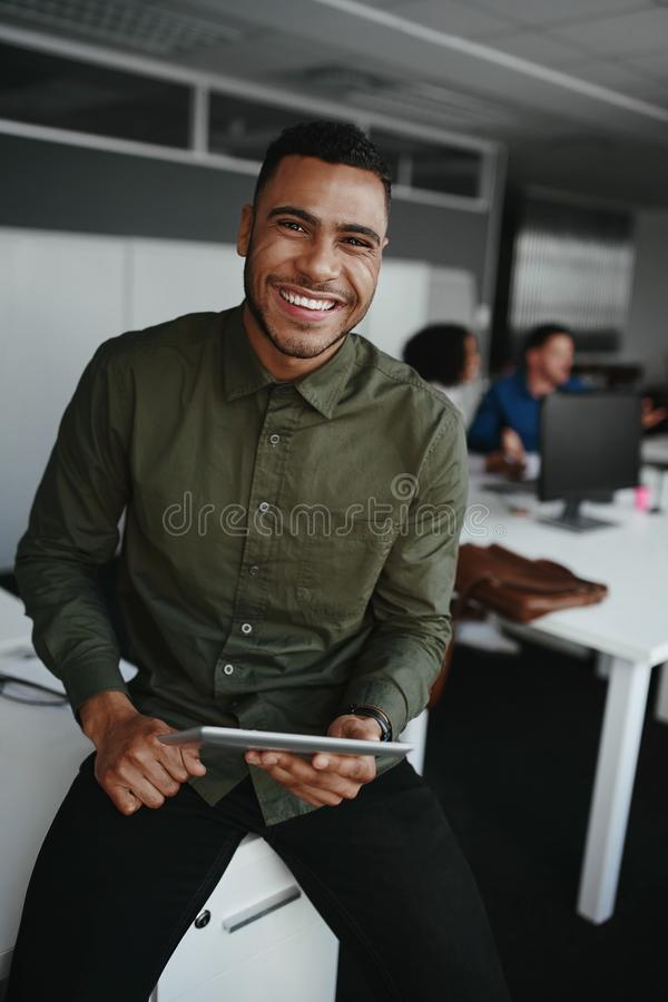 Portrait of a smiling young businessman holding digital tablet in hand looking to camera and colleague at background stock photography